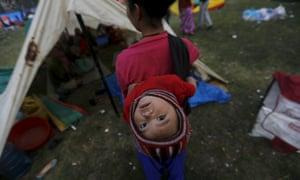 An earthquake victim carries her baby on her back as she stands outside her makeshift shelter