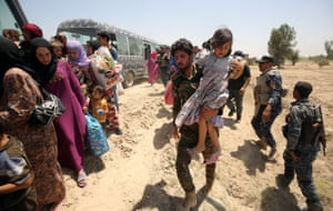 Iraqi forces help families fleeing the fighting on to waiting buses
