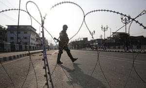 An Indian paramilitary soldier stands guard near barbed wire in Srinagar