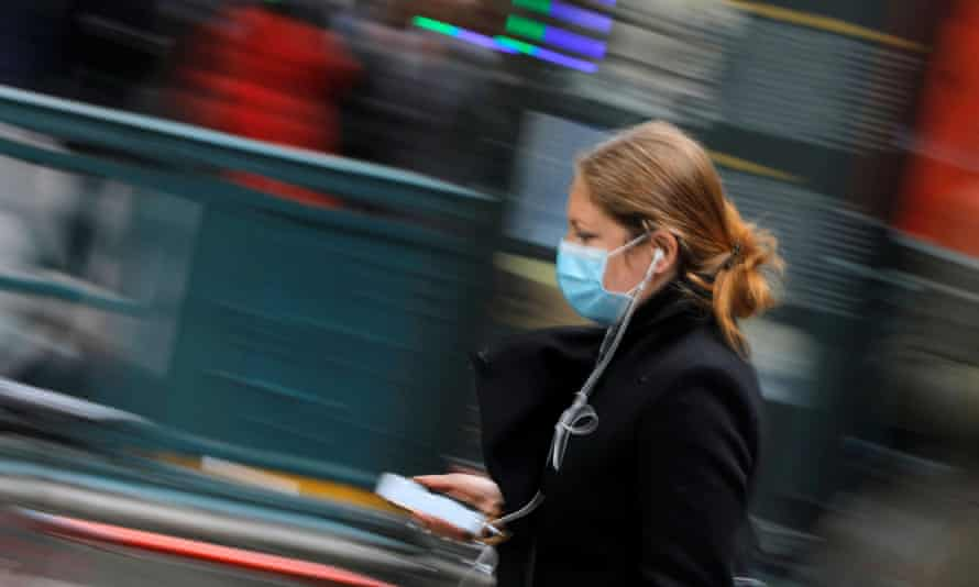 A woman in a face mask walks in New York, New York, on 5 March.