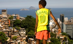 A young boy stands with a soccer ball in one of the favelas of Rio de Janeiro, Brazil.