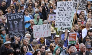 Protesters hold banners as part of the March Against Baird rally in Sydney.