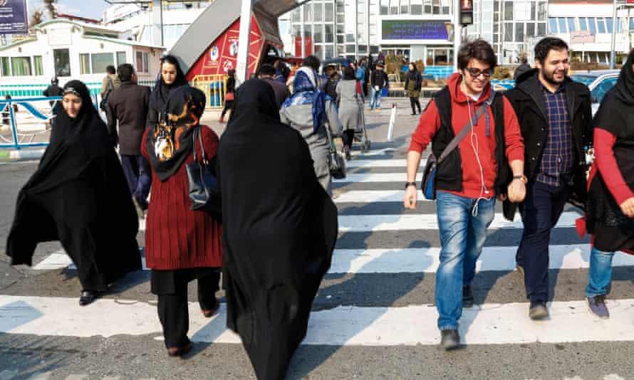Iranians cross a street in Tehran