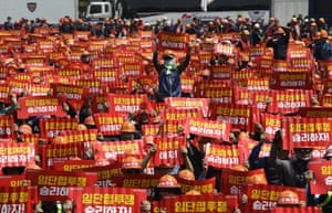Seoul, South Korea. Members of the Korean confederation of trade unions hold up their banners during a rally demanding better working conditions and expanding labour rights. The signs read 'Let's win the wage struggle'