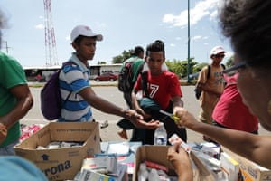 Honduran migrants receive medicines distributed by Mexican citizens during their journey to the United States, in Huixtla, Mexico, 23 October 2018.