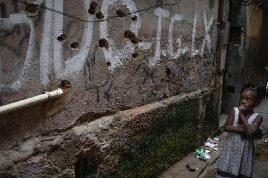 A young girl examines a bullet-riddled wall at the heart of Jacarezinho