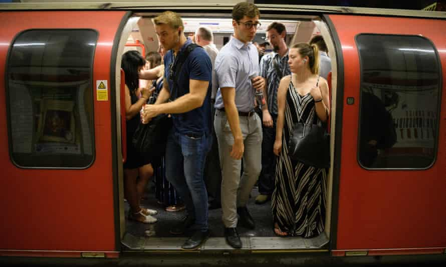 Commuters disembark from a Central Line underground train in London