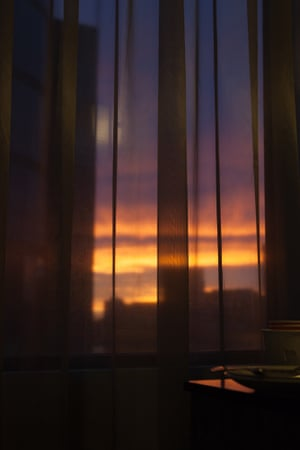View of sunset through hotel curtains