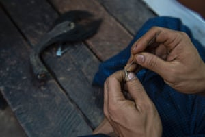 A vendor inserts an elephant hair on a ring cut from an portion of an elephants's tail for sale at one of many traditional medicine shops at Myanmar's Golden Rock Buddhist pilgrimage site