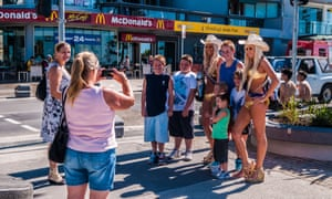 Tourists take a with a pair of Gold Coast 'meter maids'. They feed the parking meters of those who overstay so drivers can spend more time in the resort.