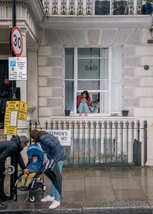 A woman sits on the window ledge of her flat in St Stephen's Gardens, while an exhausted child is shielded from the rain in a pushchair.