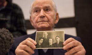 Auschwitz survivor Leon Schwarzbaum presents an old photograph showing himself next to his uncle and parents who all died at the death camp.