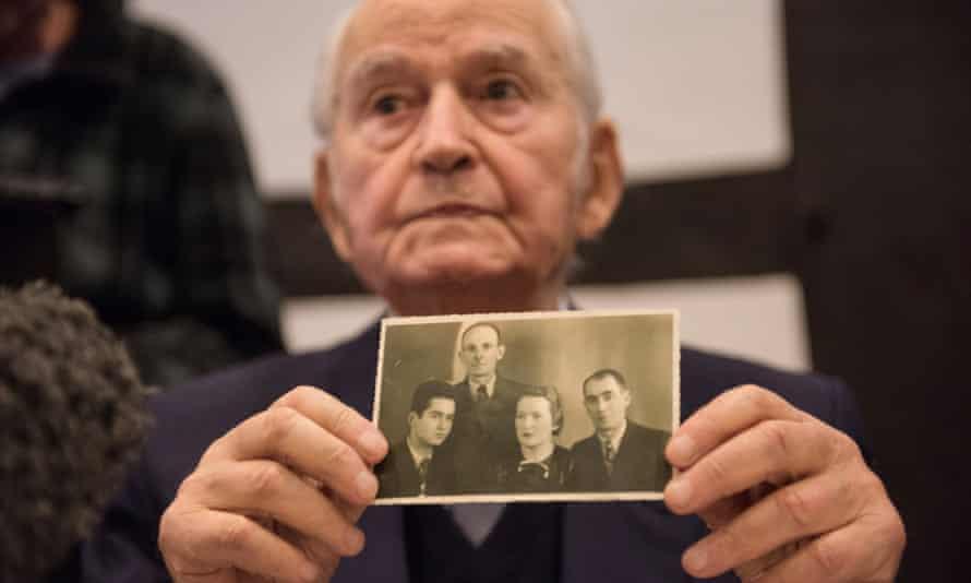 Auschwitz survivor Leon Schwarzbaum holds a photograph of family members who were killed during the second world war.
