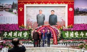 A family pose for a photograph in front of a mural of former North Korean leaders Kim Il-sung and Kim Jong-il. The portrait of the father and son leaders is at the entrance to an exhibition of Kimilsungia and Kimjongilia, flowers named in their honour, in Pyongyang, North Korea.