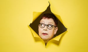Jo Brand's face appearing through a tear in a yellow background