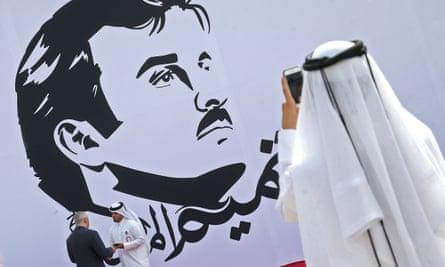 An observer takes a photograph of an image of Qatar's emir, Tamim bin Hamad al-Thani, in Doha