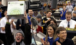 A customer holds up the first Xbox 360 video game console sold at a Best Buy store in Bellevue, as Microsoft chairman Bill Gates applauds.