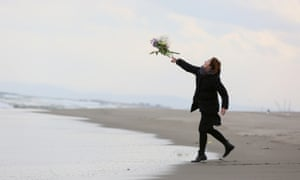 A woman throws flowers in Sendai, Japan, to mark the anniversary of the 2011 earthquake and tsunami.