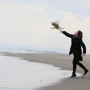 On Fukanuma beach, Sendai, a woman throws a bunch of flowers