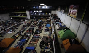 Migrants begin their day inside a former concert venue serving as a shelter, in Tijuana, Mexico.