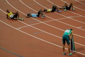 Exhausted runners lie on the track after Wayde van Niekerk had won the men's 400m final.