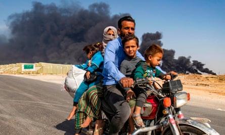 People leave an area near the Syrian Kurdish town of Ras al-Ayn
