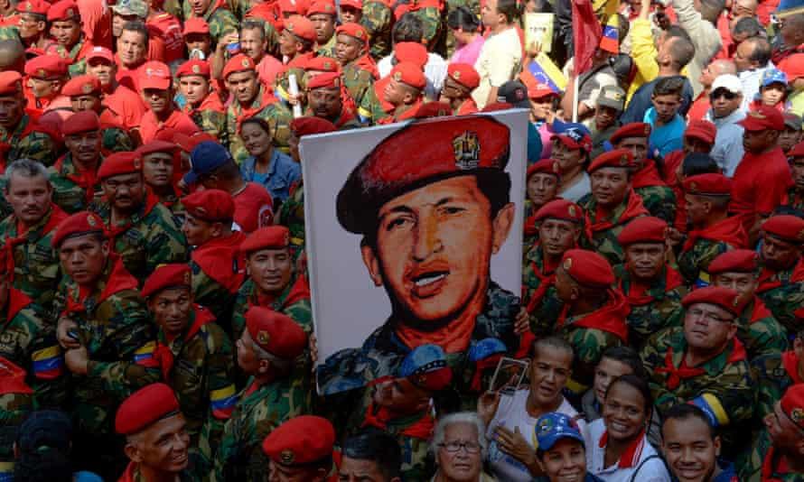 Soldiers holds a portrait of late Venezuelan president Hugo Chavez
