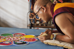 A Tibetan lama from the Sera Je monastery in India creates a sand mandala, meant to represent the cosmos in miniature.