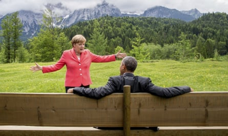 The back of Barack Obama sitting on a bench with his arms spread on the back of it and German Chancellor Angela Merkel in a pink jacket facing him with her arms spread, and a grassland and snowy mountains behind