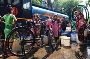 New Delhi, India. Residents fill containers with drinking water from a distribution truck during a hot summer day in the poor district of Sanjay.