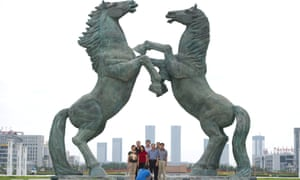 People posing beneath a statue in Genghis Khan Plaza, in the inner Mongolian city of Ordos.