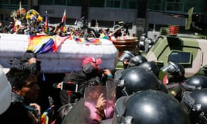 A group of people carrying a coffin attempt to pass throw a police line during a funeral procession for victims killed during clashes with police at the Senkata fuel plant in La Paz on 21 November.