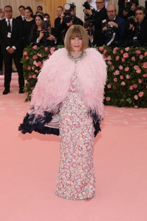"""Anna Wintour wears a pink crystal-embellished feather-laden Chanel gown inspired by the Susan Sontag quote: """"Camp is a woman walking around in a dress made of 3 million feathers"""""""
