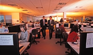 Two businessmen walking through busy office