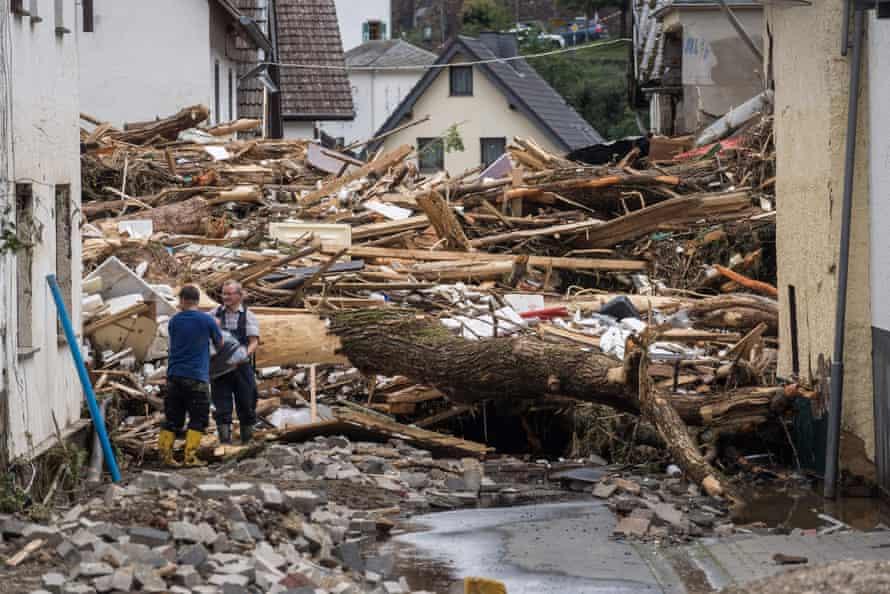 Zwei Männer entfernen Trümmer aus hochwassergeschädigten Häusern in Schultz bei Bad Nieuhner, Deutschland