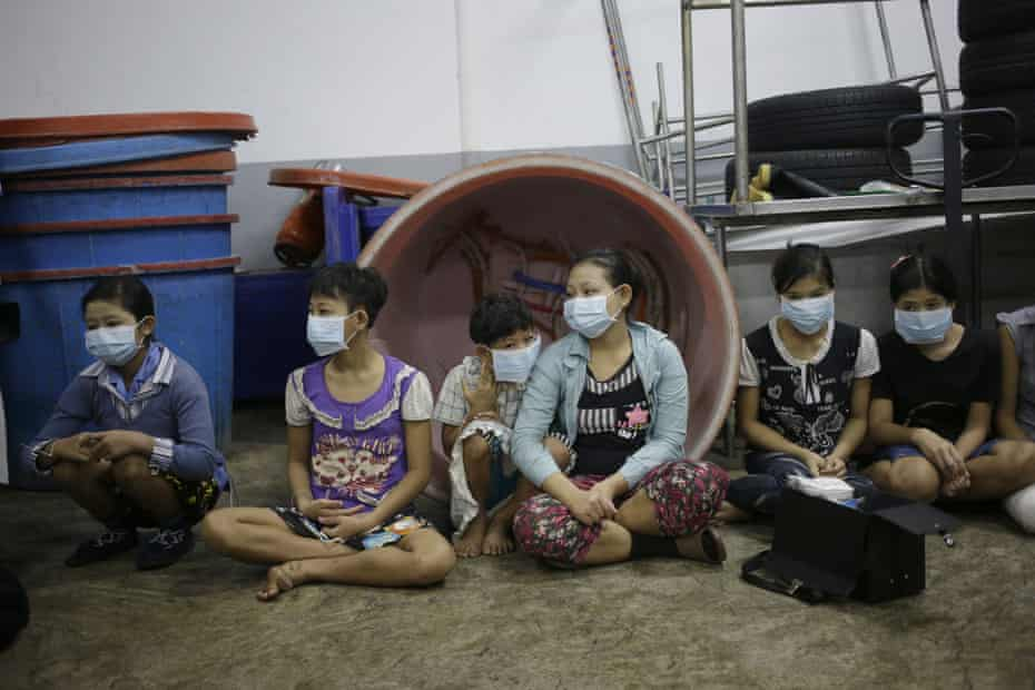 Children and teenagers sit together to be registered by officials during a raid on a shrimp shed in Samut Sakhon, Thailand, 9 November 2015