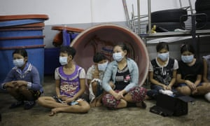Children and teenagers wait to be registered by officials during raid on a shrimp shed in Samut Sakhon, Thailand