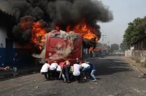 Demonstrators push a bus that was set alight during clashes with the Bolivarian National Guard, Venezuela