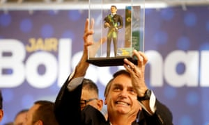 Jair Bolsonaro shows a doll of himself during a rally in Curitiba in March.