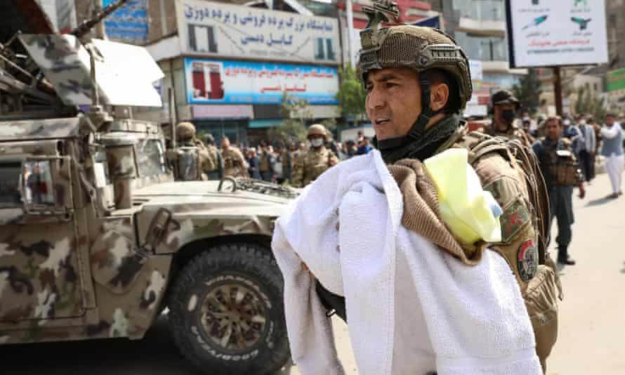 An Afghan soldier removes a baby from the hospital in Kabul.
