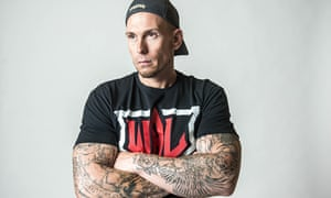 'Mighty' Paul Maiden in a t-shirt, his muscle-bound tattooed forearms crossed.