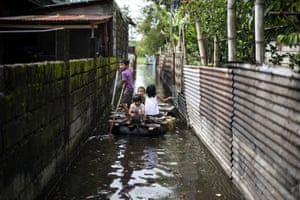 Children use a raft to cross a flooded alley in the aftermath of the storm in Calumpit, Philippines