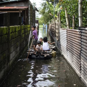 Children use a raft to cross a flooded alley in Calumpit, Bulacan, after Typhoon Mangkhut