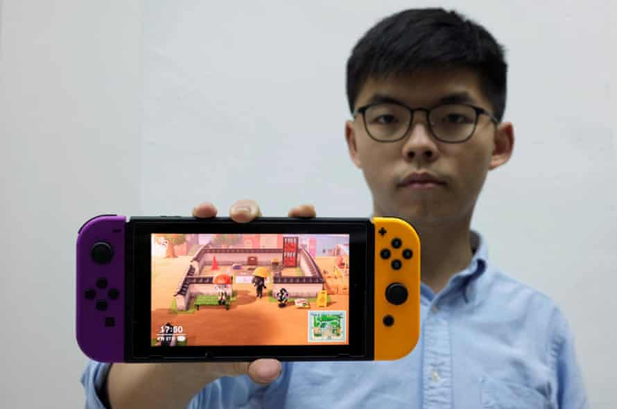 """Pro-democracy activist Joshua Wong poses with a Nintendo Switch where depictions of anti-government protesters and signs saying """"Free Hong Kong"""" are seen in the game Animal Crossing."""