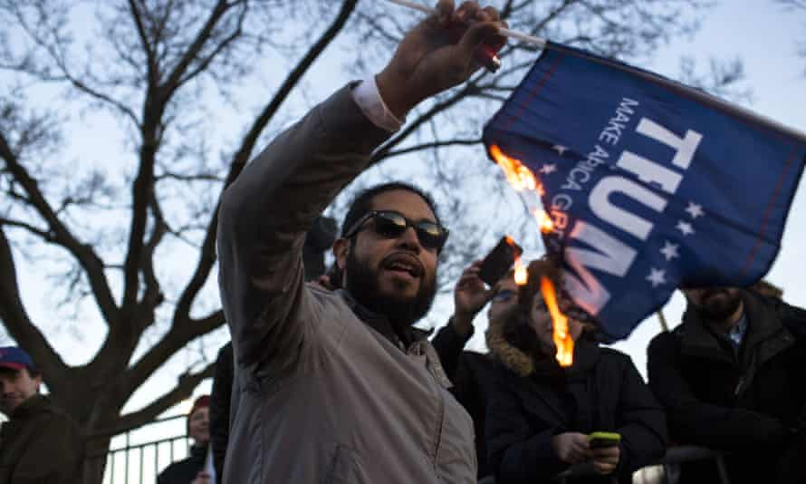 A protester burns a Trump campaign flag outside the venue.