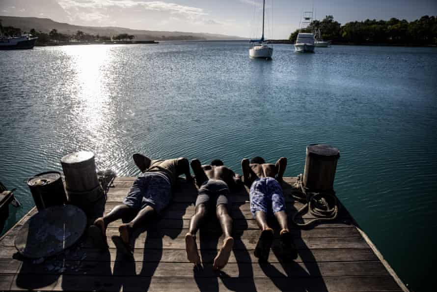 Morris Gause, Nigel Simpson and Andre Ramator peer over the end of a dock to look at fish in the Oracabessa fish sanctuary.