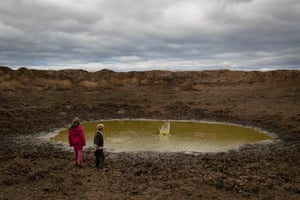 Heidi, 7, and Harry Taylor play in one of the many empty dams on their family farm.