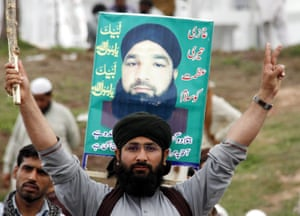 Supporters of Mumtaz Qadri hold his photo during a protest outside the parliament building in Islamabad.