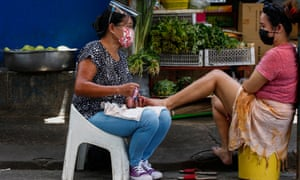 A woman gets a pedicure outside a market stall in Marikina City in Metro Manila, among the coronavirus pandemic in the Philippines 14 September 2020.