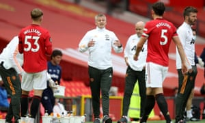 Manchester United's manager, Ole Gunnar Solskjær, talks to two of his defenders – Brandon Williams and Harry Maguire – during a break in play against West Ham.